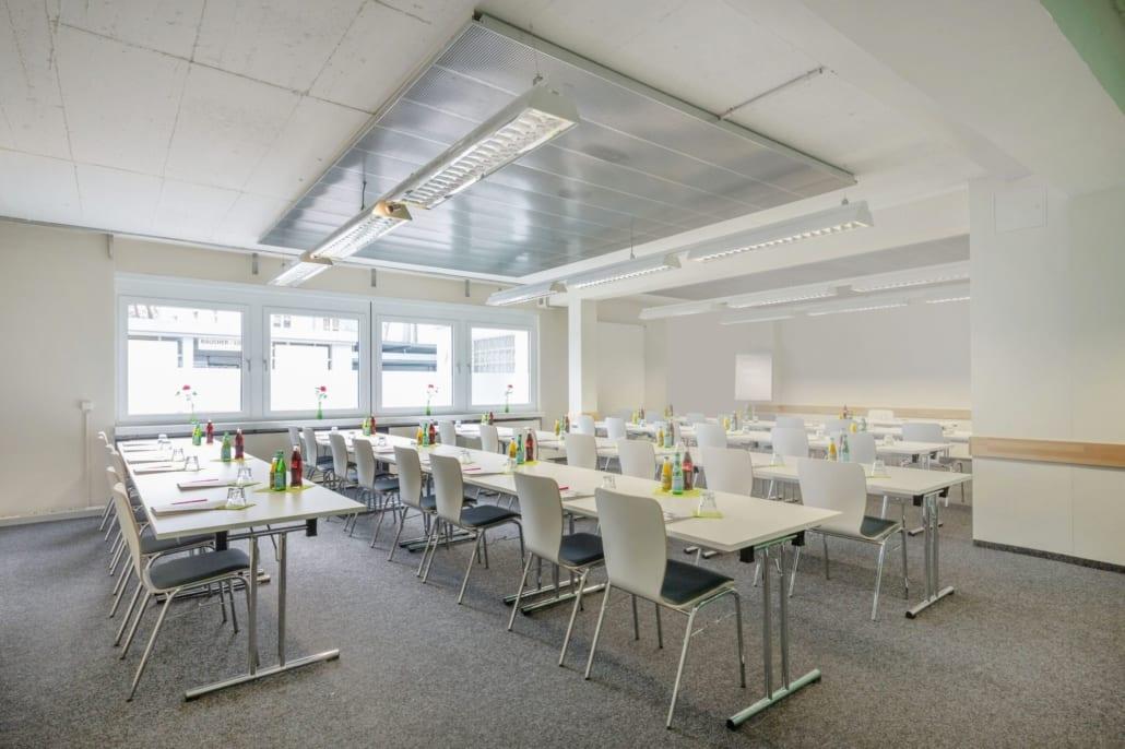 Moderner Tagungsraum mit vielen Tischen und Stühlen und Blick nach draußen
