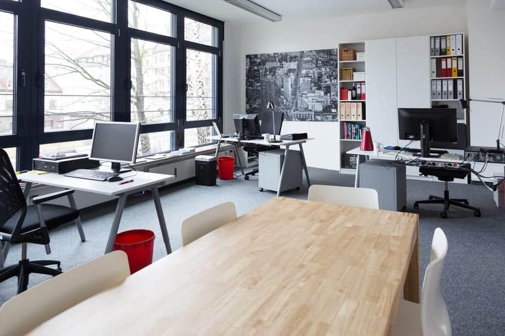 Hellbeleuchteter Raum mit Arbeitsplätzen und einem großem Meetingtisch