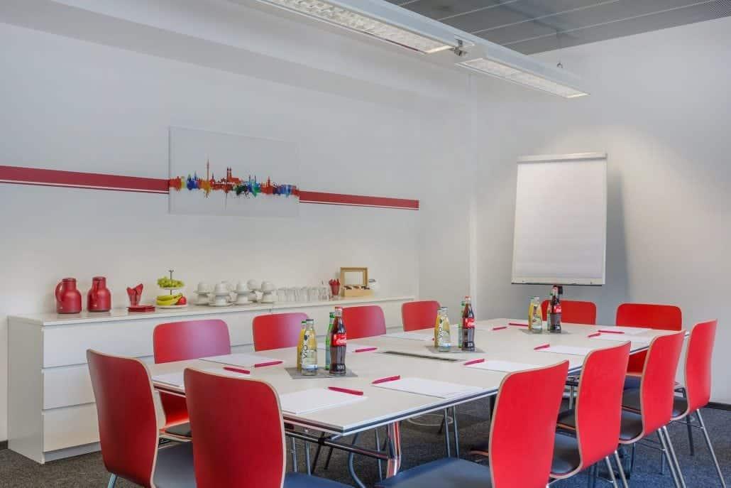 Meetingraum mit roten Stühlen an einem großem Konferenztisch mit einem Flipchart