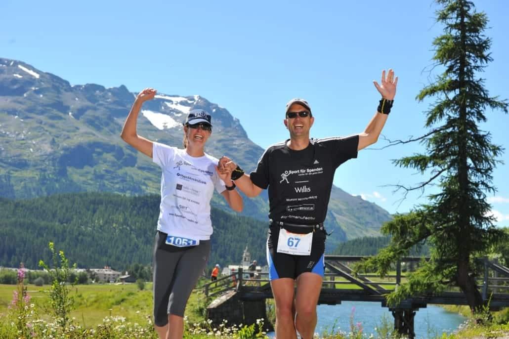 Zwei Läufer in den Alpen im Hintergrund die Berge und ein Fluss.