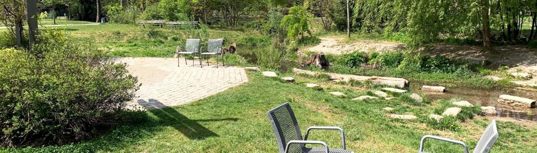 Park mit Stühlen und kleinem Bach