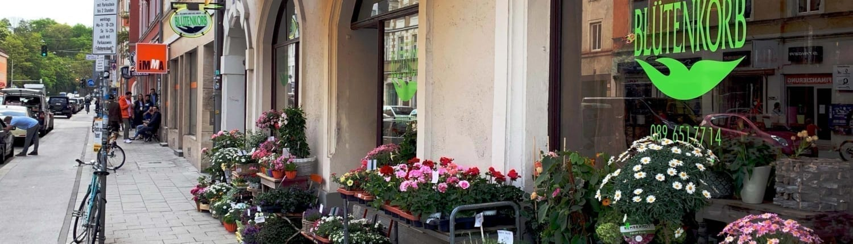 """Gehweg an Straße bei Tag mit Blumenladen """"Blütenkorb"""" im Fokus"""