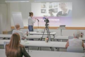 Seminarraum, Blick ueber Reihen nach vorn, Moderator zeigt Beamerpraesentation, Kamera für Livestream