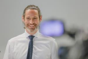 Lächelnder Moderator in Hemd und Krawatte vor der Kamera
