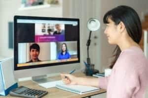 Frau mit Notizblock am PC während Online Videocall
